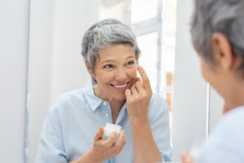 Baby Boomer woman using lotion