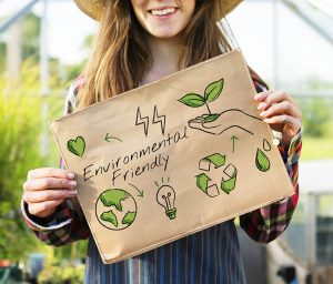 A woman farmer holding a sign saying Environmental Friendly | Sustainability and Barrier Packaging