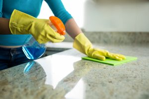woman cleaning with spray triggers